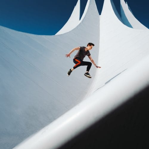 An agile person jumping on the roof of a white building roof