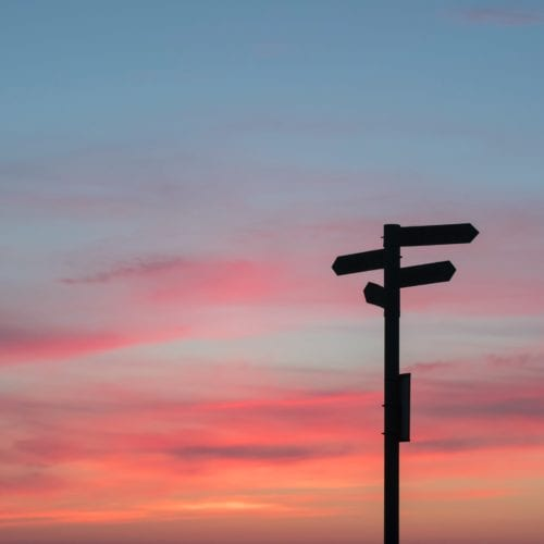 Signpost against a red sky